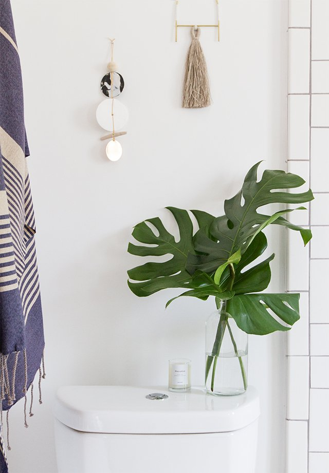 Adding greenery to your bathroom is an easy and affordable way to add life back into a dreary space. Want to find out other ways to makeover your bathroom? Check out 13 Easy Ways to Freshen Up Your Bathroom. #vanity #hardware #bathroom #interiors #tips #makeover #affordable #bathroomupgrade #plants #monstera