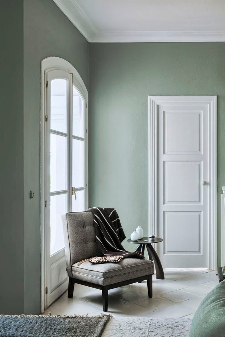 Photo of sage green seating area in traditional bedroom.