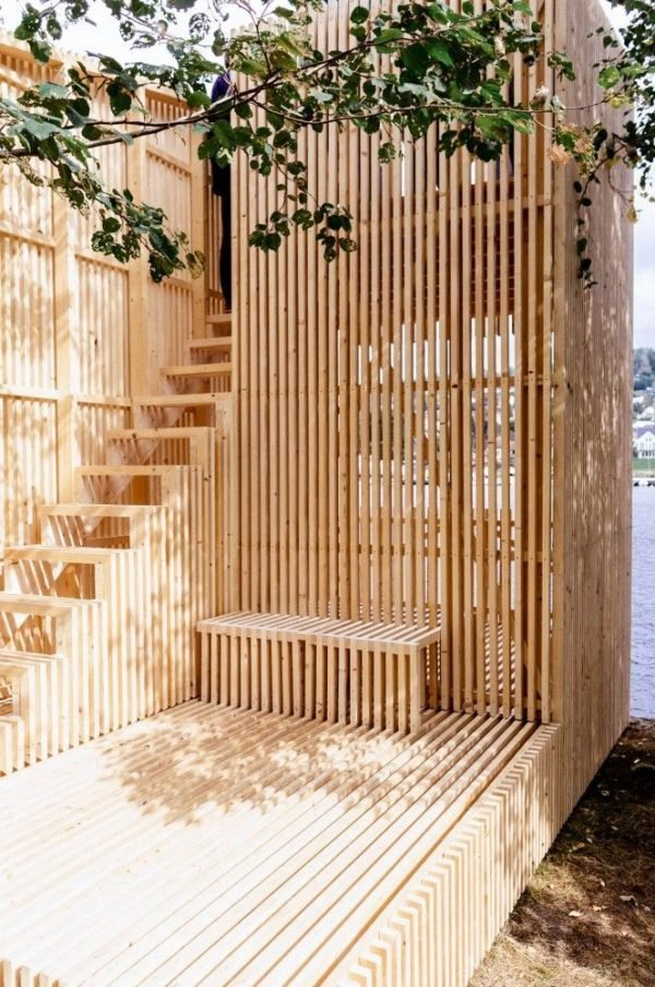 "Check out this outdoor installation by Kollaboratoriet using slatted wood partitions. See how to ""Step Up Your Staircase Game with This Modern Design Trend"" #staircase #stairs #stairscreen #moderndesign"