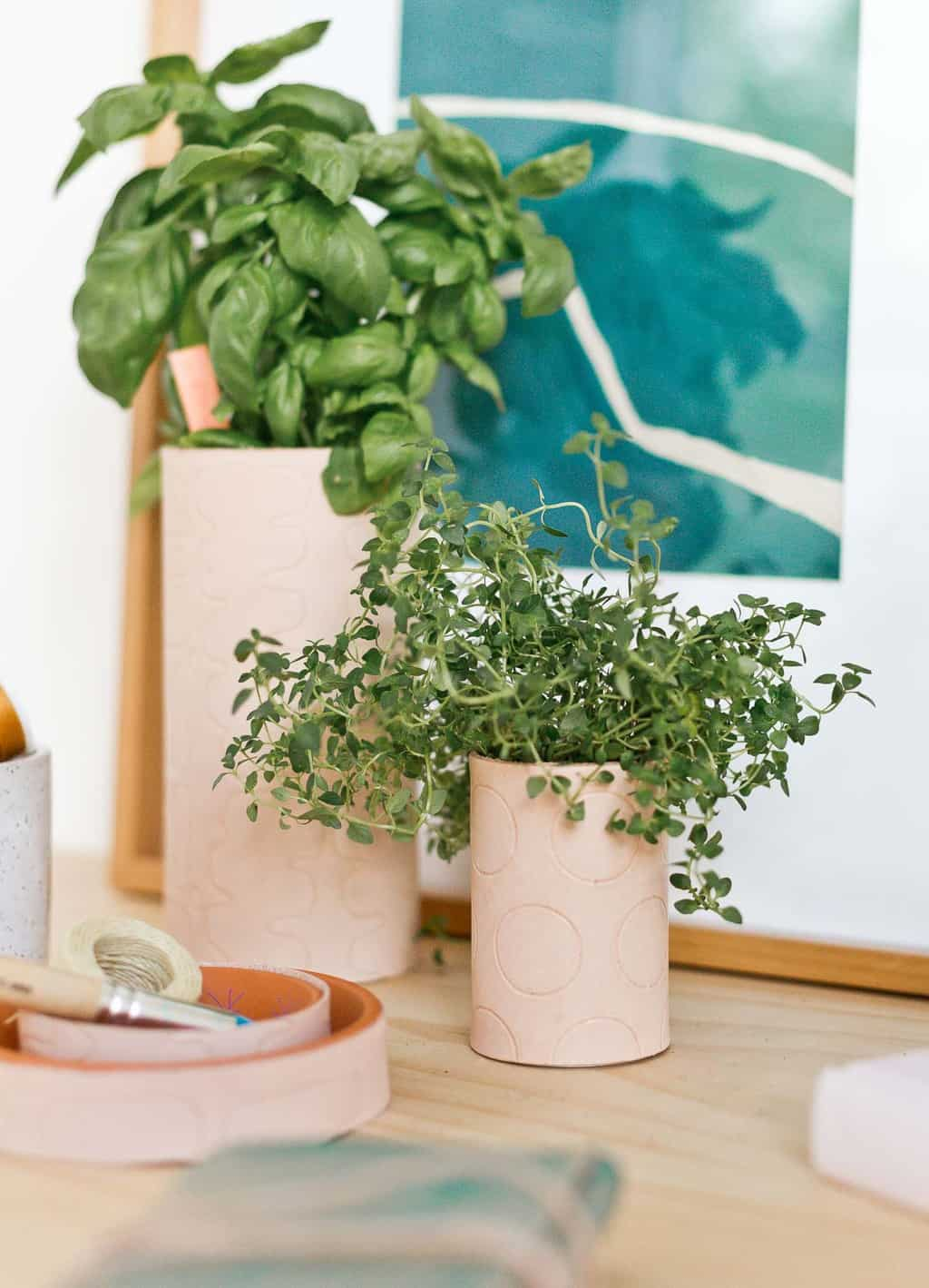 Leather planters with polka dot pattern embossed on them and herbs inside, on a wood desk