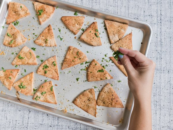 Bake pita pieces to make the 'chips'. Click through for the hummus board recipe.