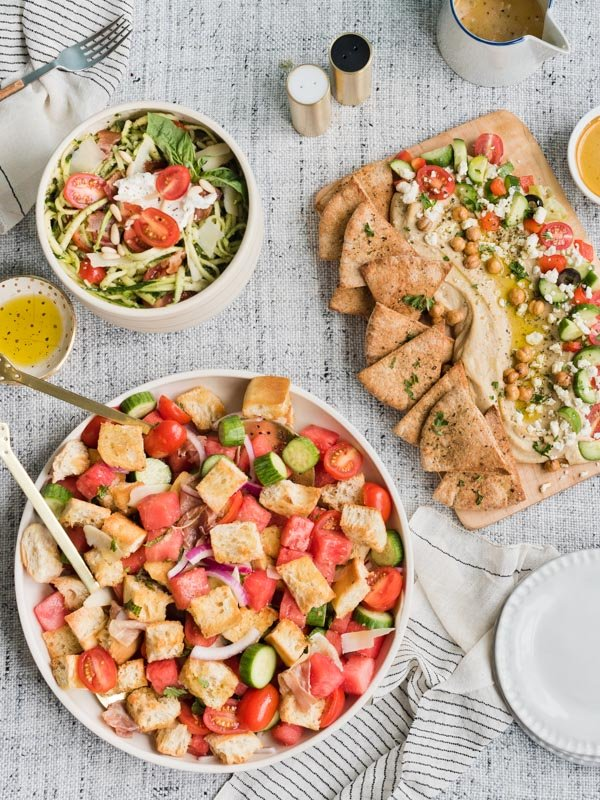 Overhead image of three different summer salads on a table ready to enjoy.