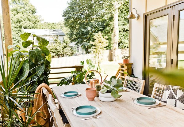 A small(ish) back porch gets a makeover, from completely empty to comfortable and stylish - Paper and Stitch. #porchmakeover #outdoorinspiration #modernoutdoorliving #organicmodernliving #outdoormakeover #outdoorentertaining