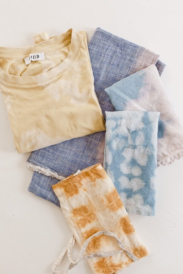 Photo of reverse tie dye shirt, bandanas, and napkins in muted colors, all stacked up.