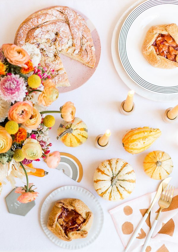 A unique Thanksgiving tablescape that is minimal and modern, but still cozy and colorful. Complete with beeswax candles, hand stamped linens, DIY florals, and more. #thanksgiving #tablescape #tabledecor #entertainingideas #thanksgivingentertaining #thanksgivingdiy
