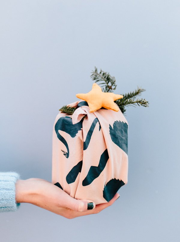 Looking for a unique DIY gift wrap idea for the holidays? Check out this tutorial for DIY fabric gift wrap you can customize for everyone on your gift list. #holidays #giftwrap #diyholidays #diy #stenciling #christmas #christmasdiy