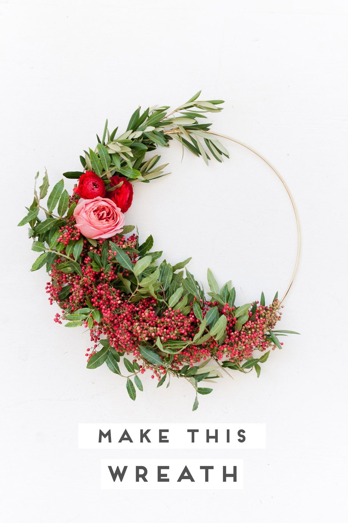 Unique holiday wreath made of red berries, pink flowers, and greenery.