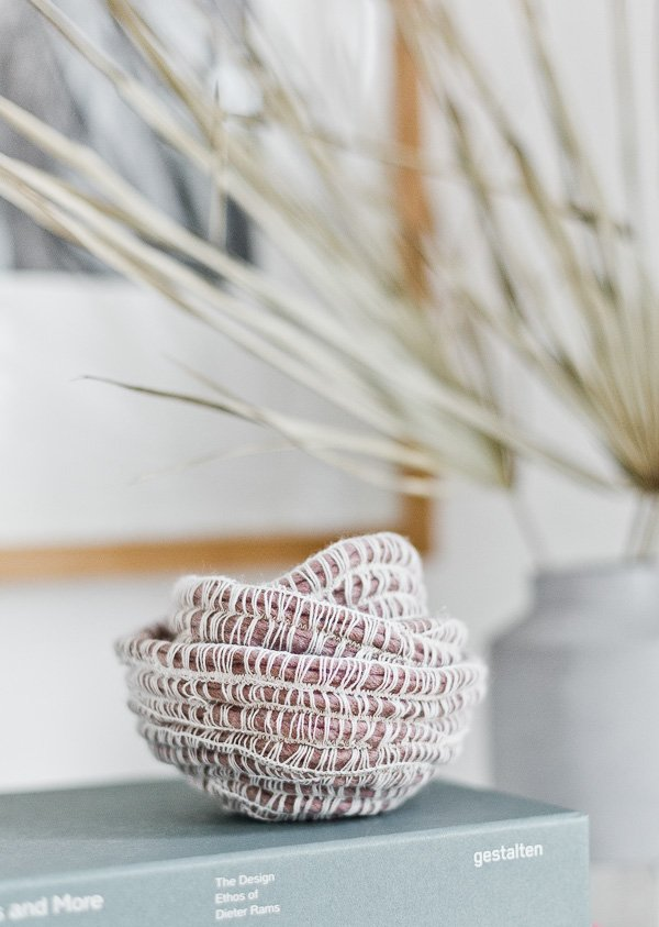 Simple yarn baskets in a mauve color, resting on a grayish blue book.