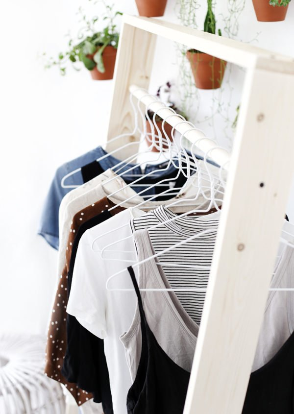 A wood clothing rack with white metal hangers hanging clothes from the clothing bar.