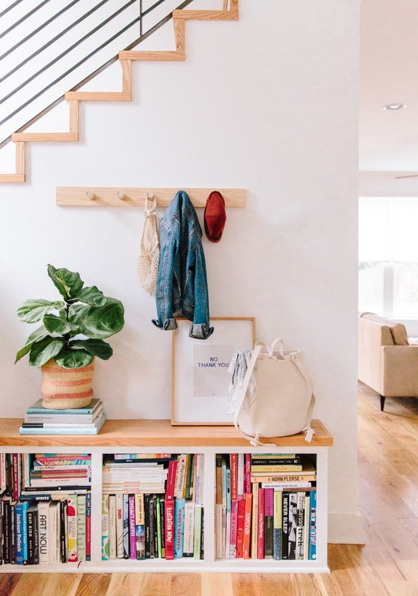 A simple wood peg rail hangs on the wall, underneath the stairway of a modern home.