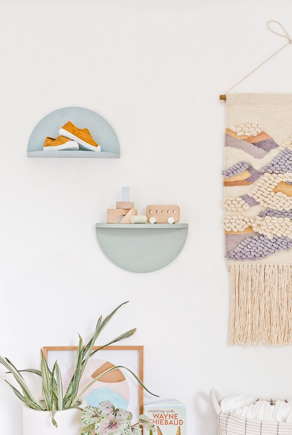 Pastel half circle wall shelves hanging in a gender0neutral nursery.