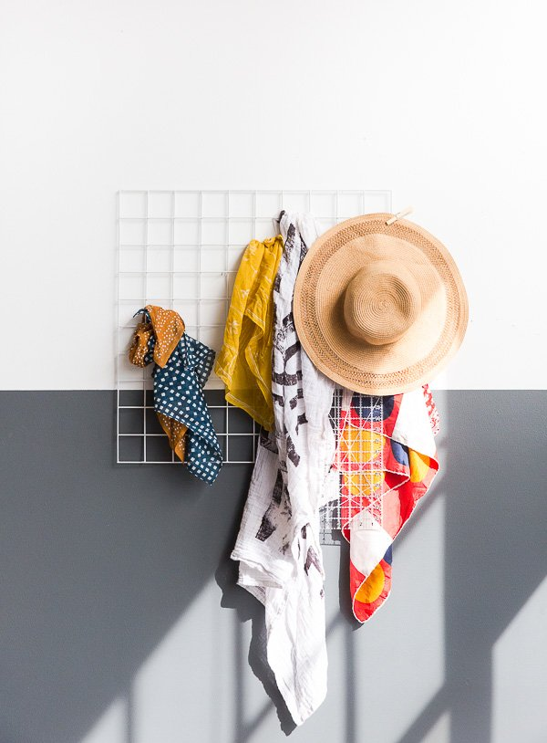 A grid wall storage rack on a color blocked wall.