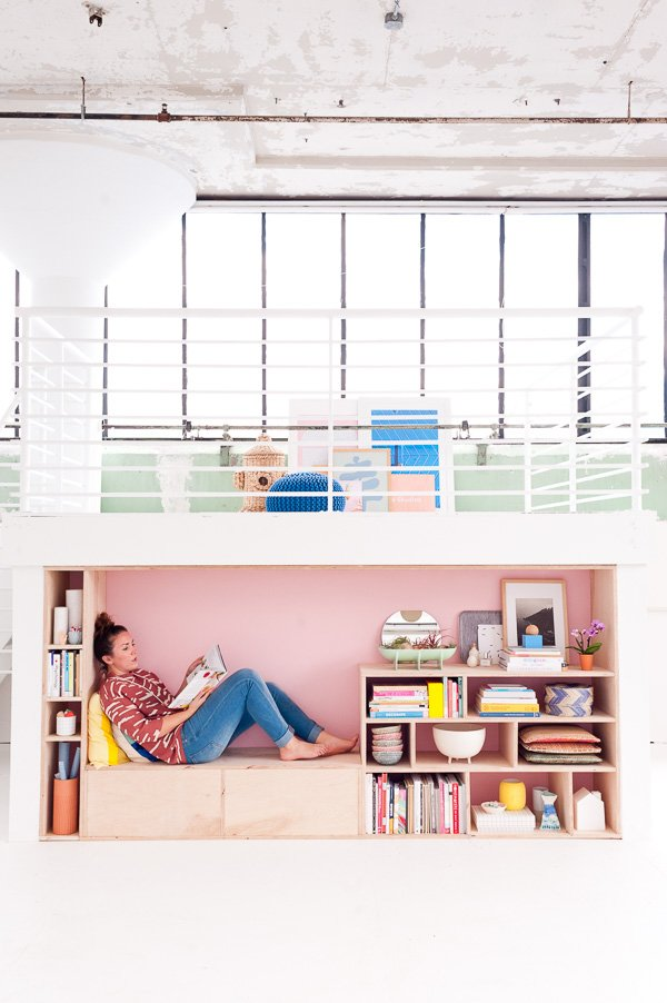 A colorful loft space with wood storage for books, vases, and other decorative items.