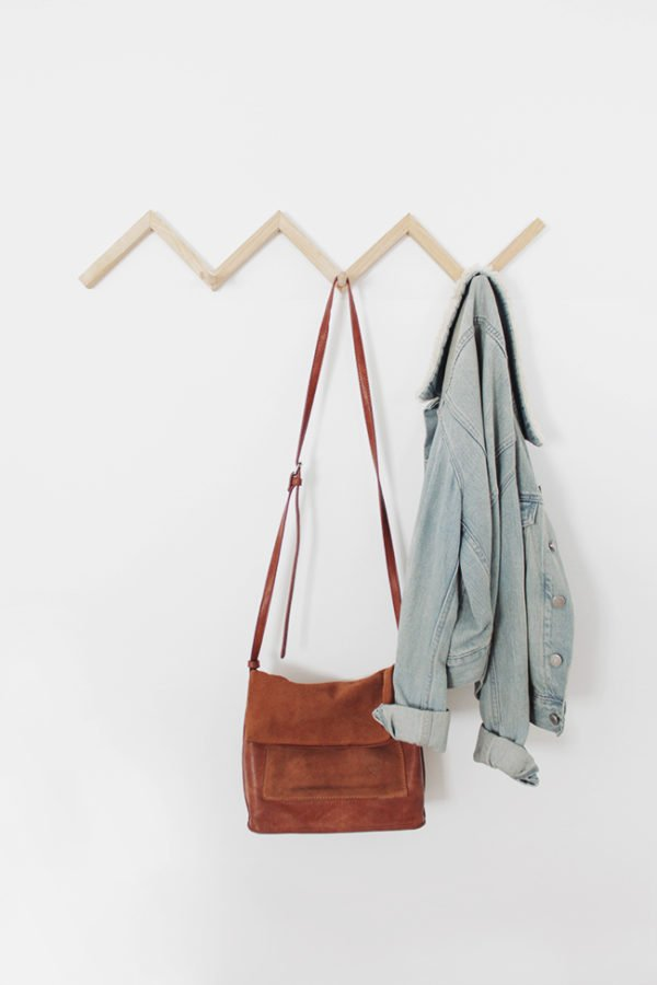 A wood zig zag coat rack hangs on a white wall with a jean jacket and a brown purse.
