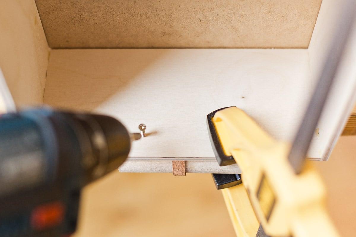 Screwing DIY drawer pulls into drawer. Click through for the tutorial. #diy #drawerpulls #wood