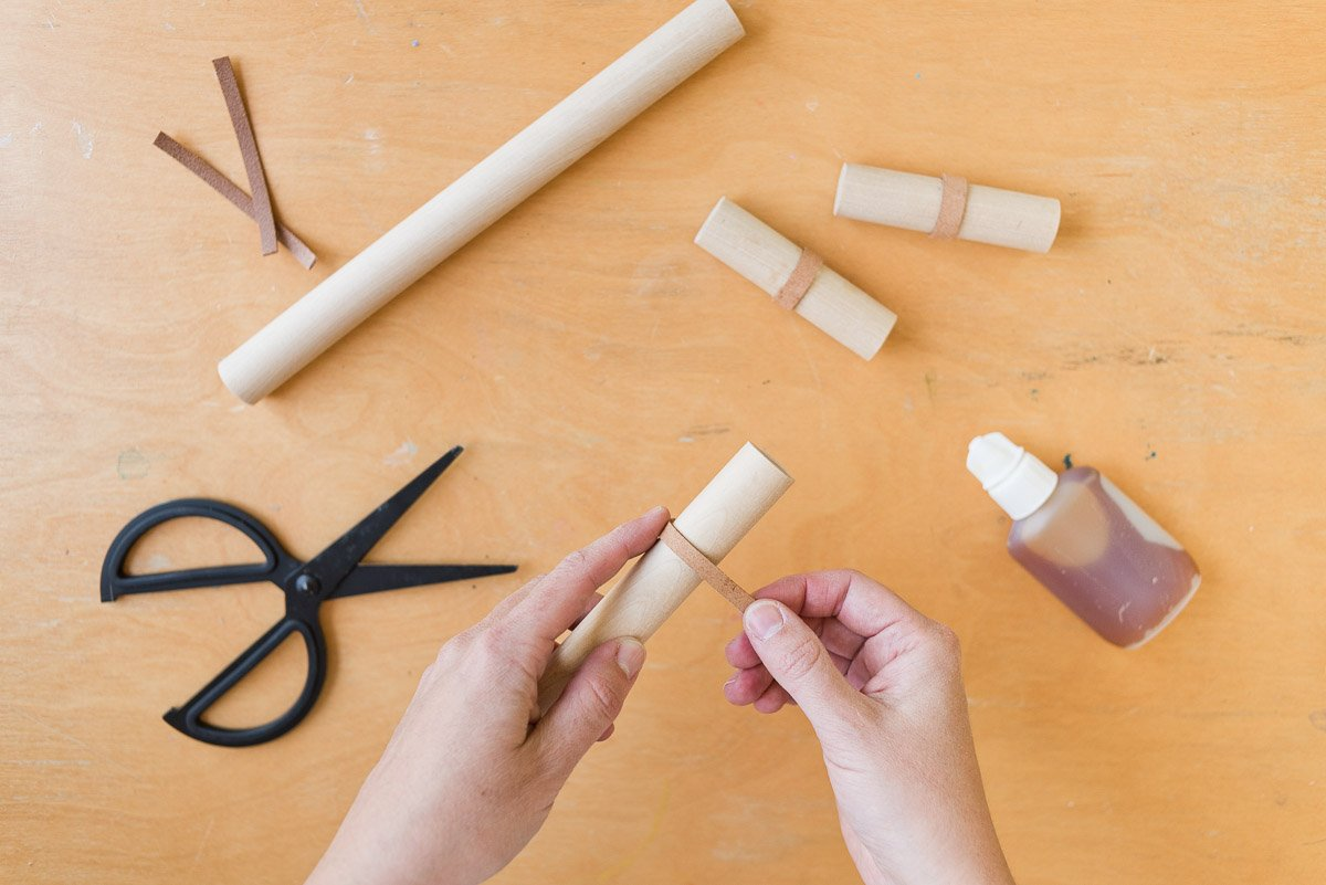 Wrapping leather around wood dowel rods for DIY drawer pulls. Click through for the tutorial. #diy #drawerpulls #wood