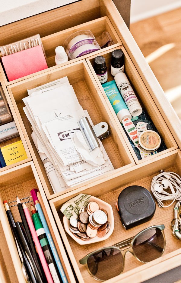 Image of an organized drawer with wooden cubbies to section things items.
