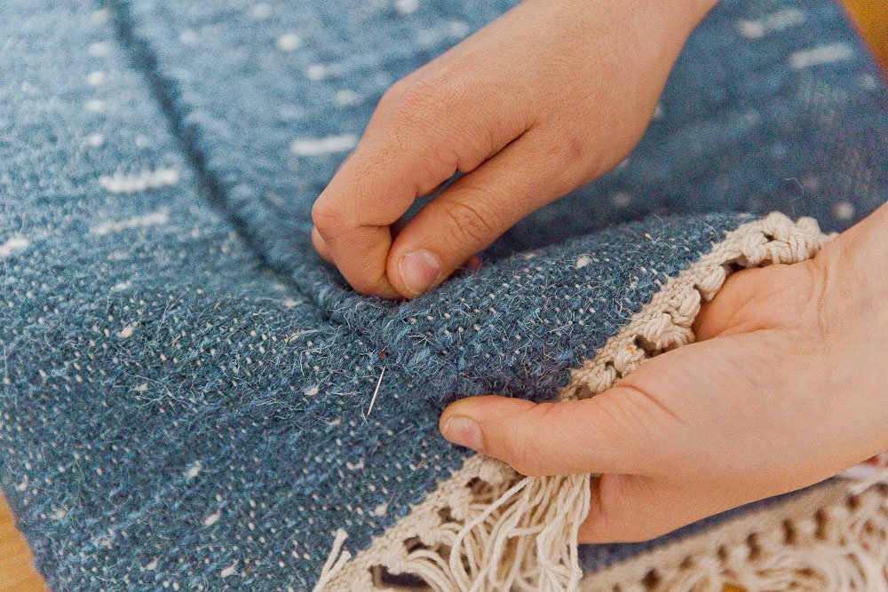 Hand stitch the length of the rug to create the pillow pocket.