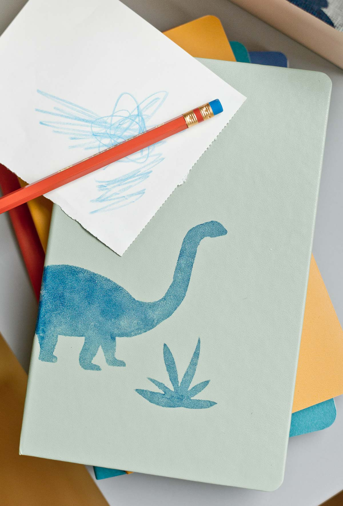Add something custom to a plain notebook for back to school with a simple stencil. This dino and plant were stenciled on using a little paint and a stencil dauber. Click through for the DIY details (and more back to school ideas). #diy #organization #backtoschool #kidscrafts #notebook #dinosaur