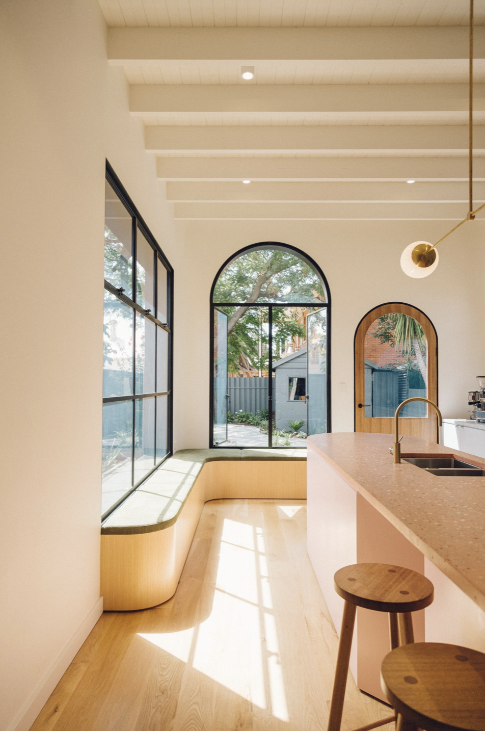 These arched windows and doors from Sans Arc Studio make this space feel extremely playful and elevated at the same time. I love the contrast of the dark window frame and mullionsand the light wood door. #arch #designtrend #interiors #organicmodern #kitchen #archwindow #archdetail