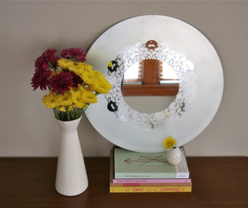 Frosted glass mirror with a doily design pattern, sitting on a walnut dresser.