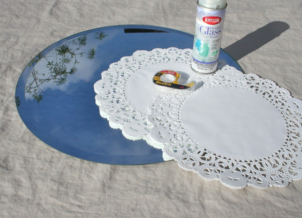 Materials needed to make a frosted glass doily mirror.