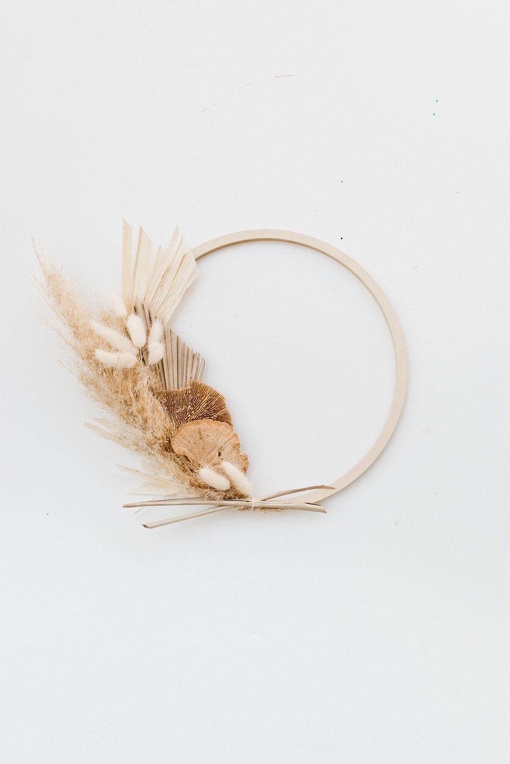 An asymmetrical fall wreath made of pampas grass, wheat, and palm leaves.