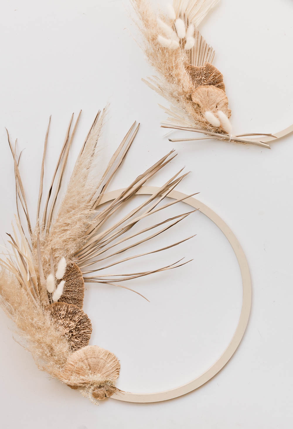 Two modern asymmetrical fall wreaths - made of pampas grass, wheat, and palm leaves.