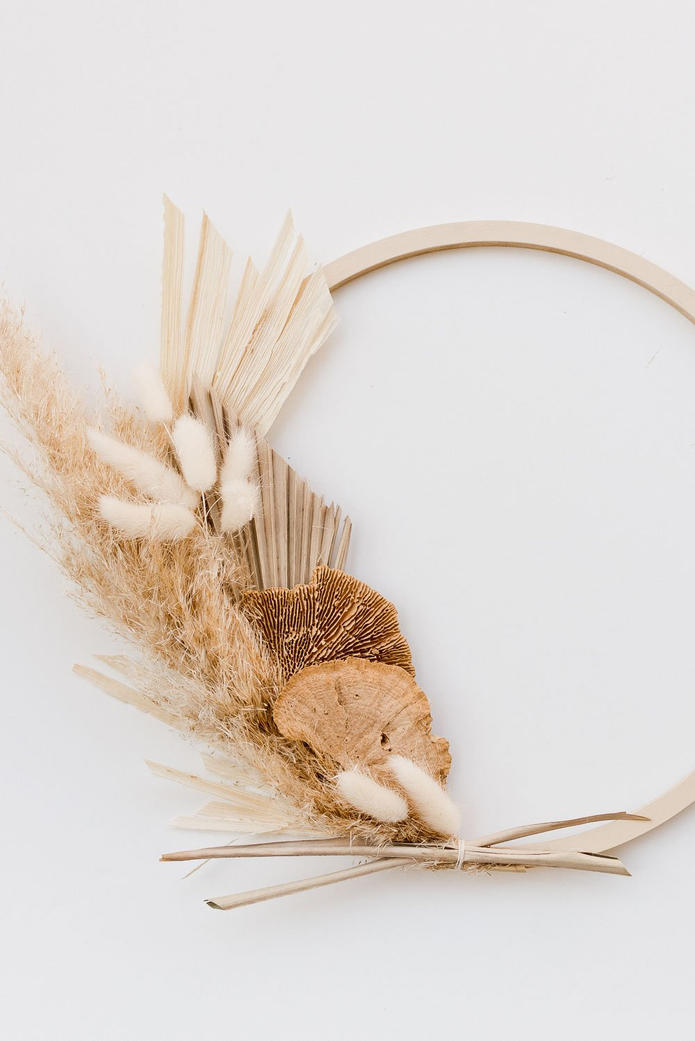 Image of an asymmetrical fall wreath made of pampas grass, wheat, and palm leaves.