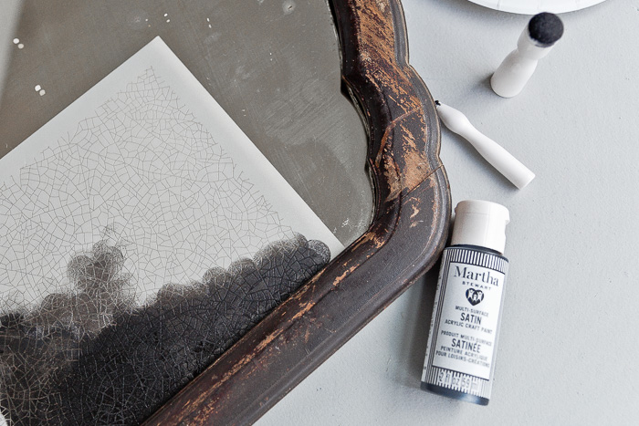 Closeup of painting stencil onto mirror.