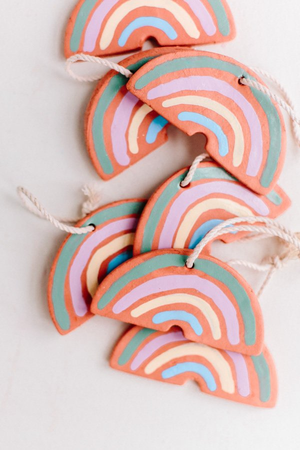 Clay rainbow ornaments stacked on top of each other with natural twine