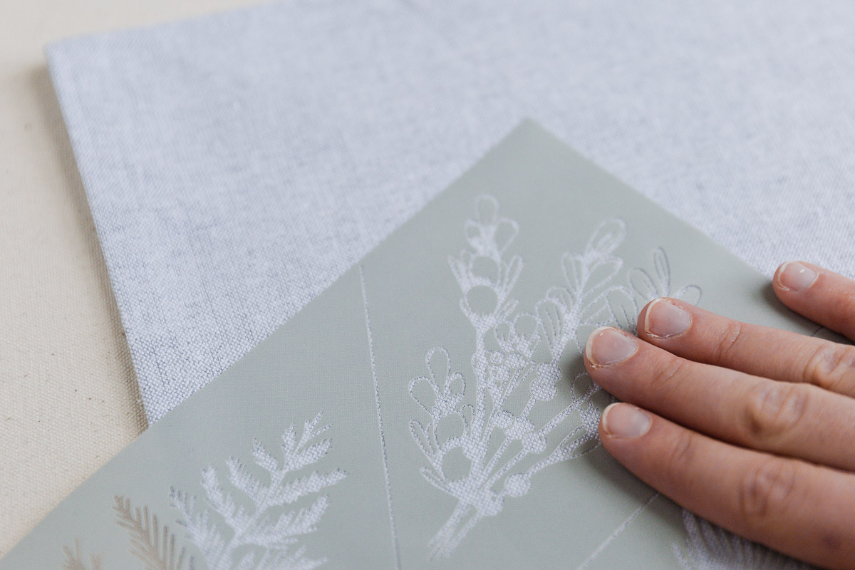 Apply floral stencil to fabric napkin