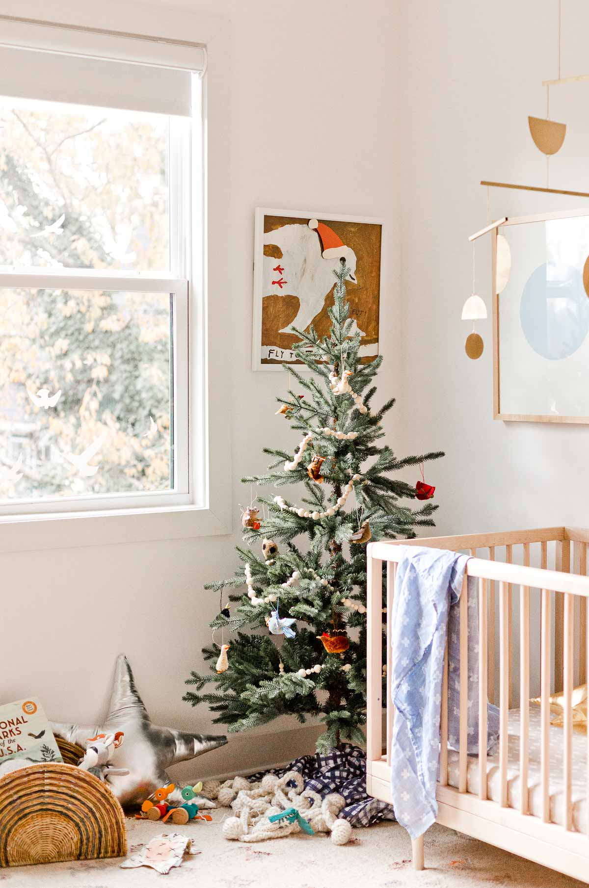 I like the simplicity of this holiday inspiration - a simple Christmas tree in a kid's room or nursery, mixed with metallic star pillows and Santa hats on the artwork.