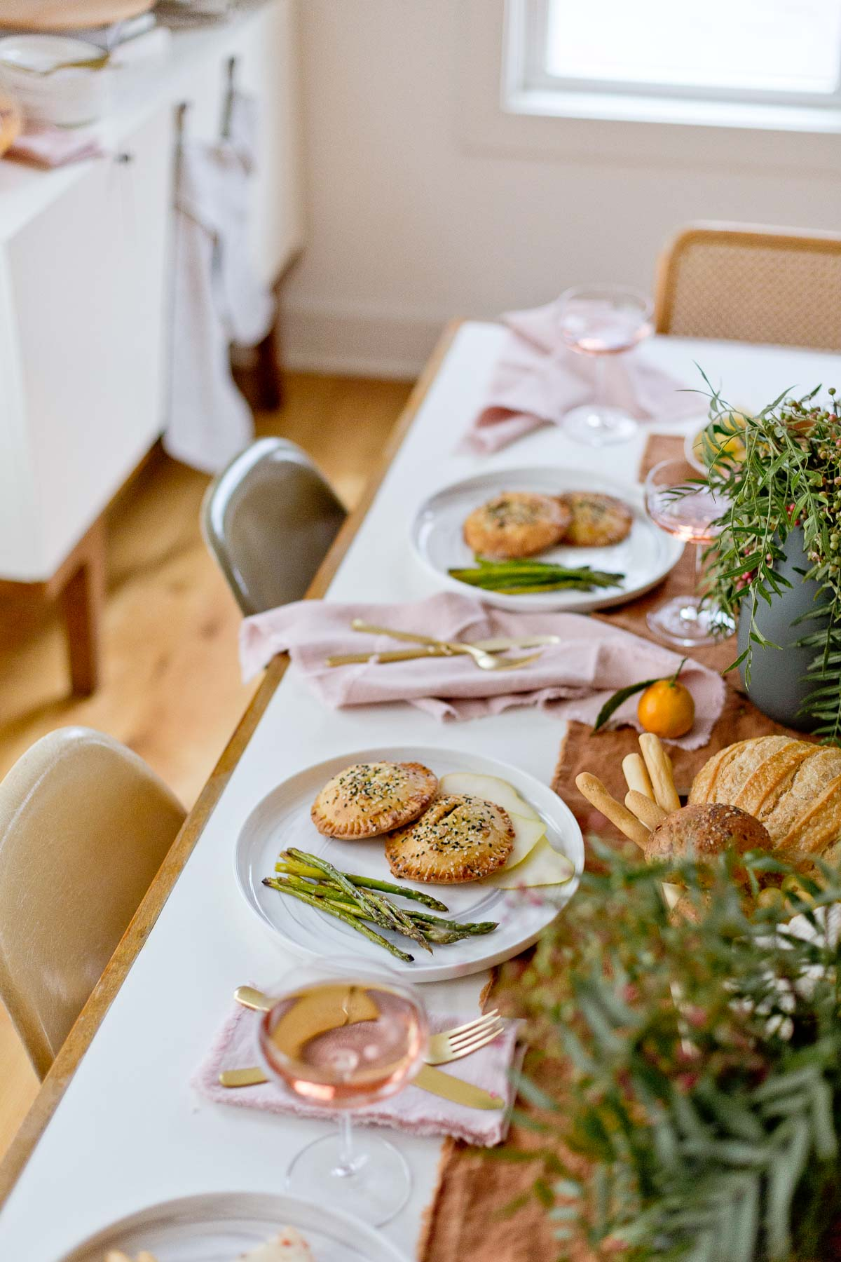 Overhead shot of holiday entertaining dining table with hand pies, asparagus, and wine.
