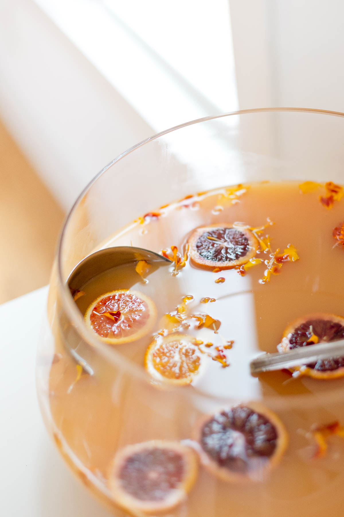 Holiday punch with blood orange and satsuma orange slices and edible flowers