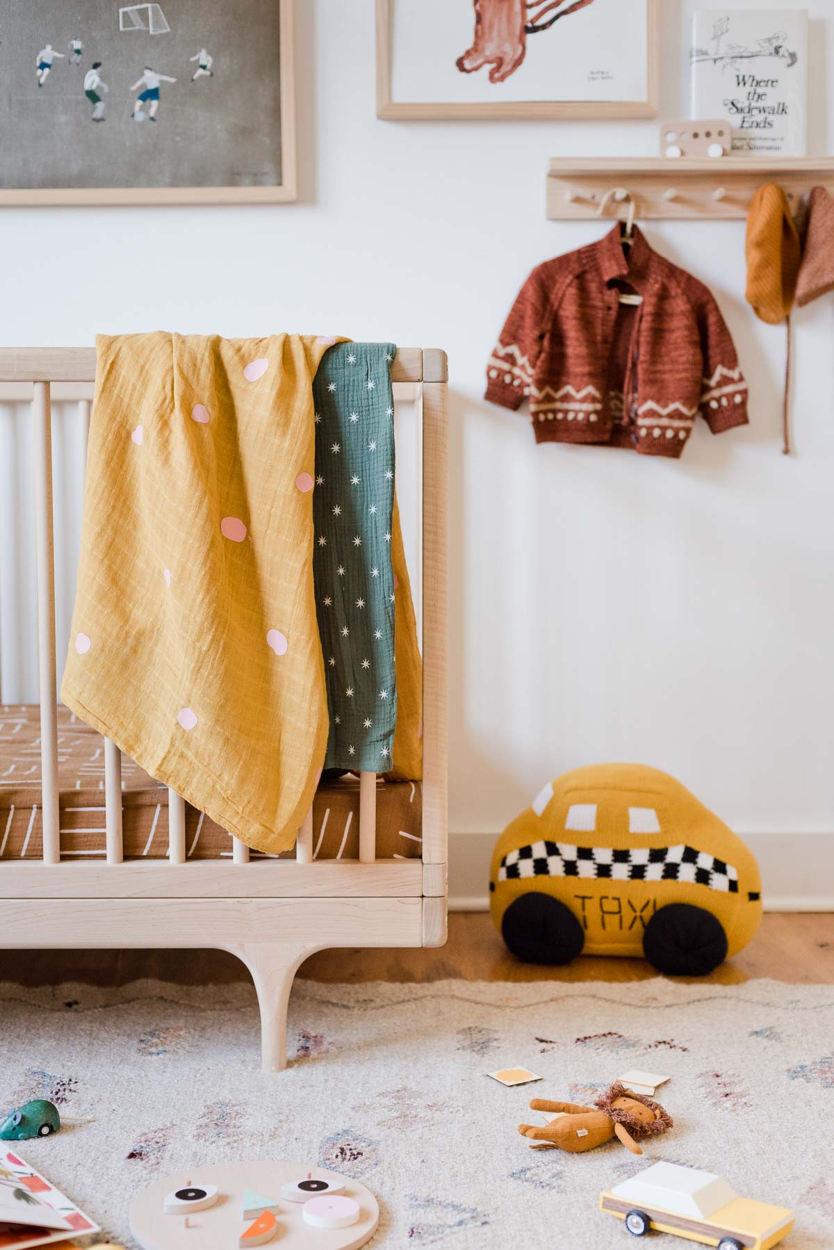 Gender neutral nursery with colorful blankets hanging over crib