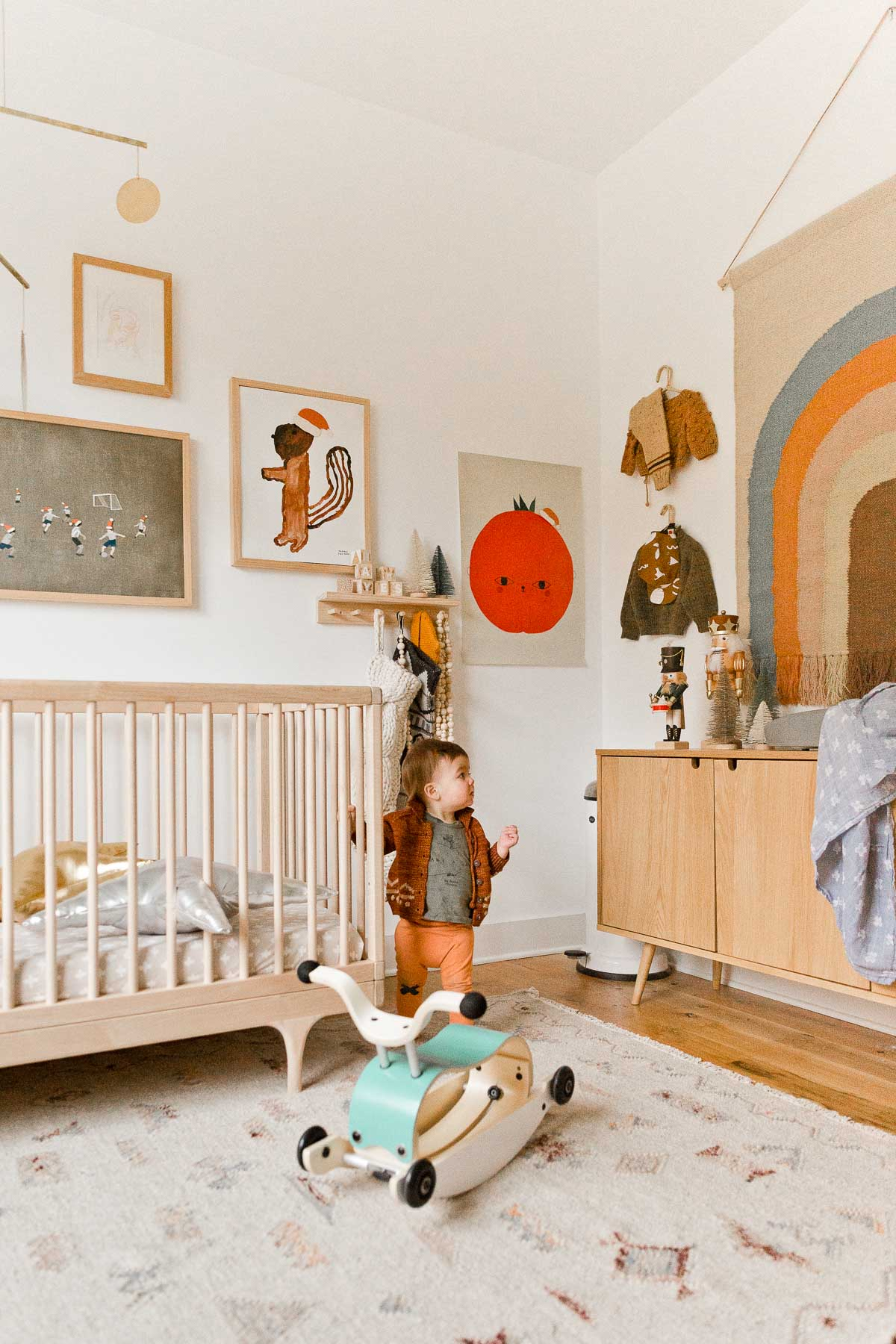 A simple, neutral nursery with a few holiday touches - stockings hanging from a peg rail, nutcrackers on the changing table, Santa hats on the artwork, etc.