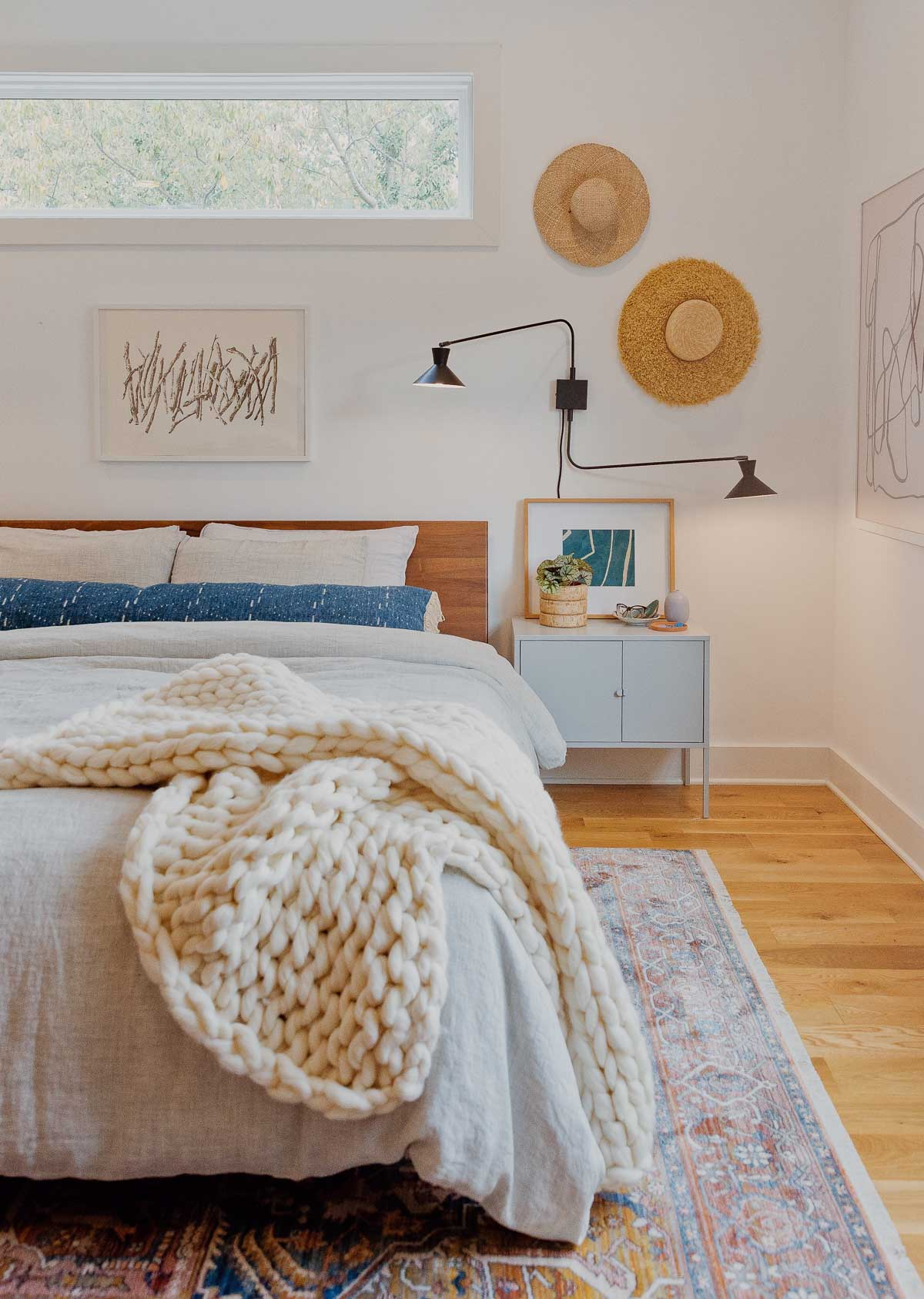 A thick, cozy knit blanket hangs off the edge of a platform bed.