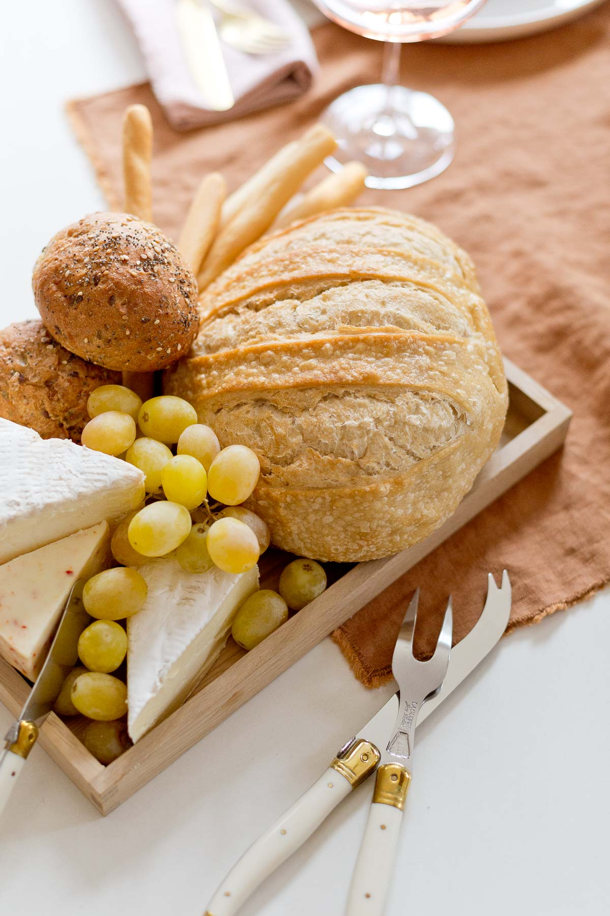 Bread tray with slices of cheese and grapes on a rust colored table runner
