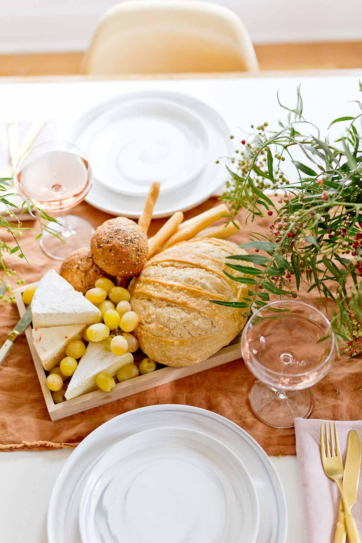 Bread and cheese tray with grapes and wine