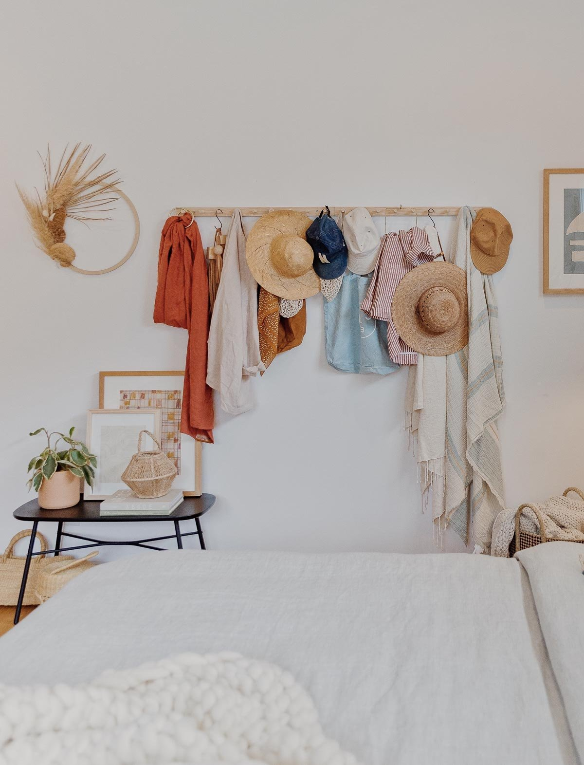 A wood peg rail hangs on a white wall with hats, scarves, and bags.