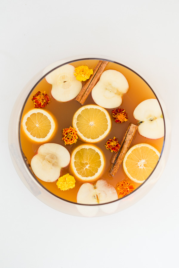 Overhead view of spiked cider punch for the holidays, with orange and apple slices, cinnamon sticks, and edible flowers.