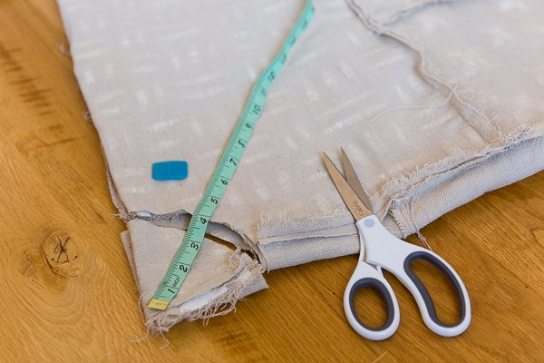 Cutting hole into tree skirt with scissors and measuring tape