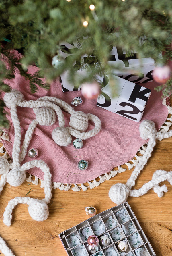 Pink Xmas tree skirt with tiny tassels and presents under the tree
