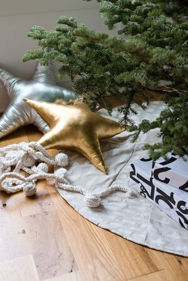 Patchwork Xmas tree skirt with metallic star pillows and cozy knit garland under the tree