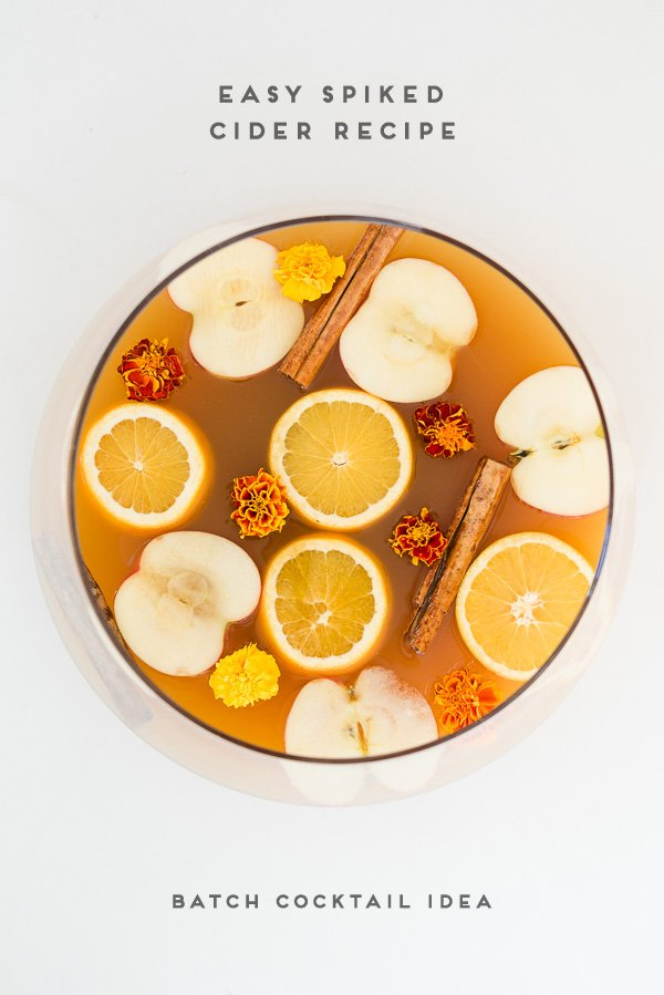 Easy spiked cider recipe in a punch bowl with sliced oranges and apples
