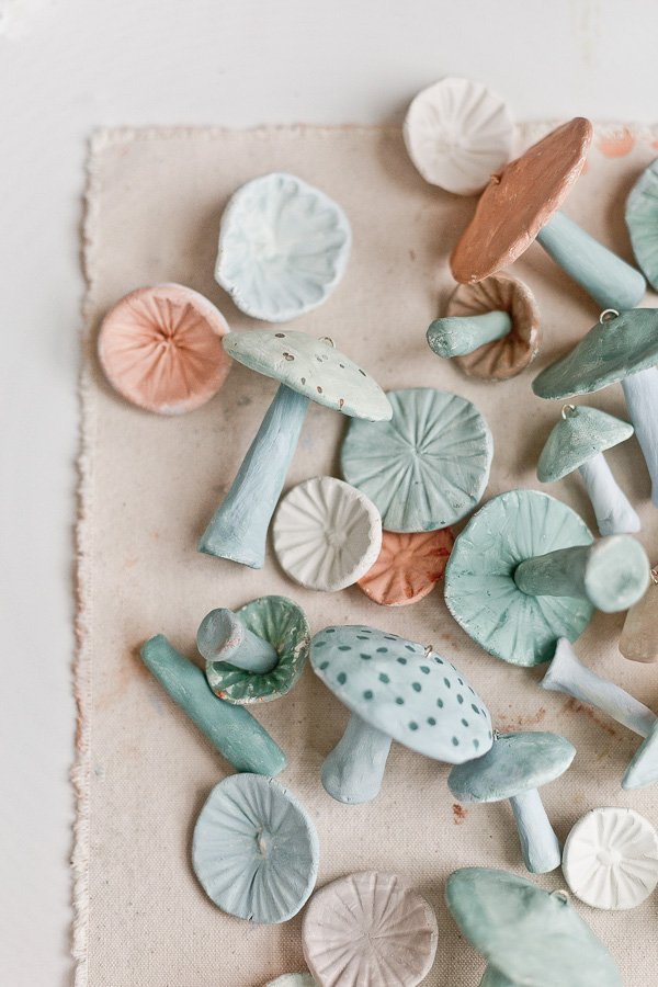 Image of clay mushroom ornaments on canvas background in various earthy green and tan colors.