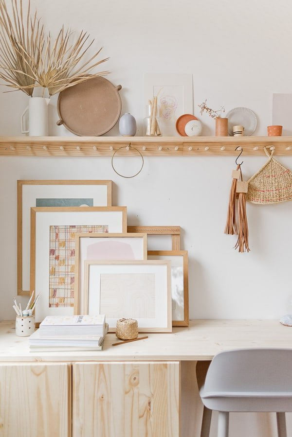 Stacked artwork and a long peg rail in a home office filled with DIY touches