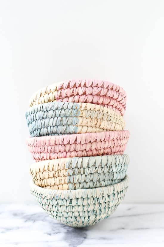 Dyed baskets for organizational storage, stacked on a marble surface.