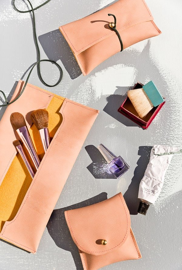 Simple leather pouches that store makeup brushes and keep other small items organized.